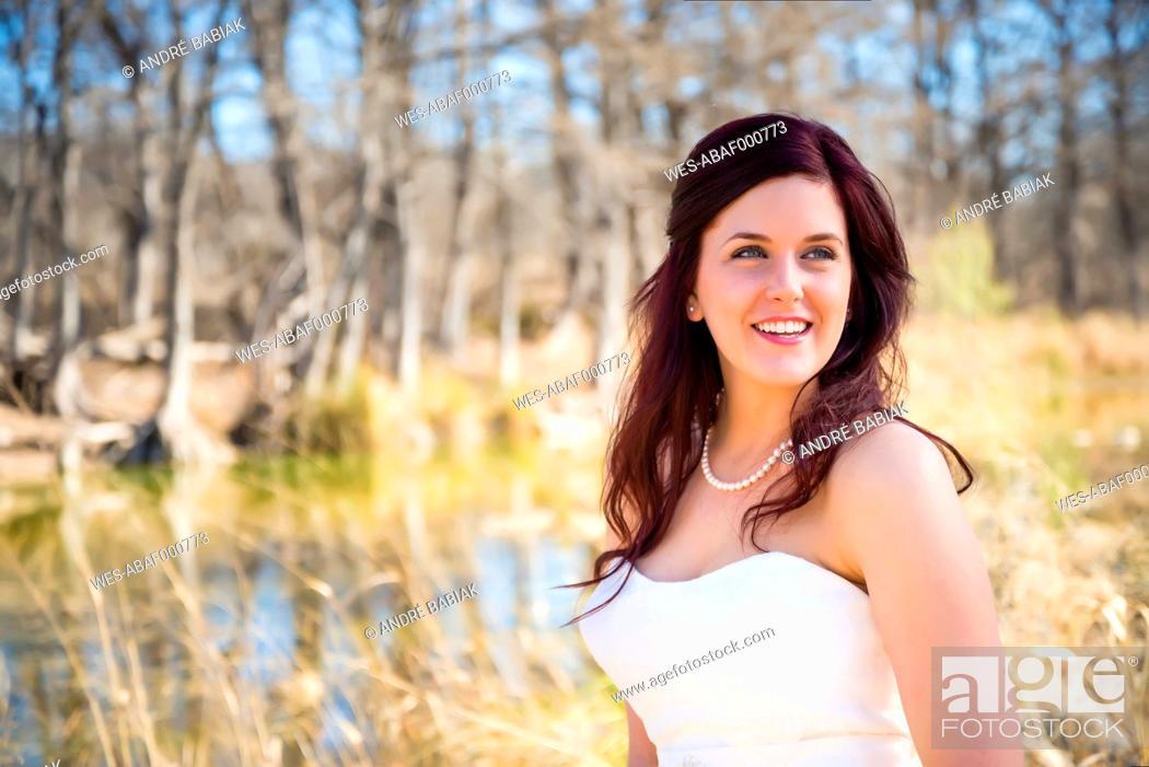Stock Photo: USA, Texas, Young bride in wedding dress posing at Frio River.