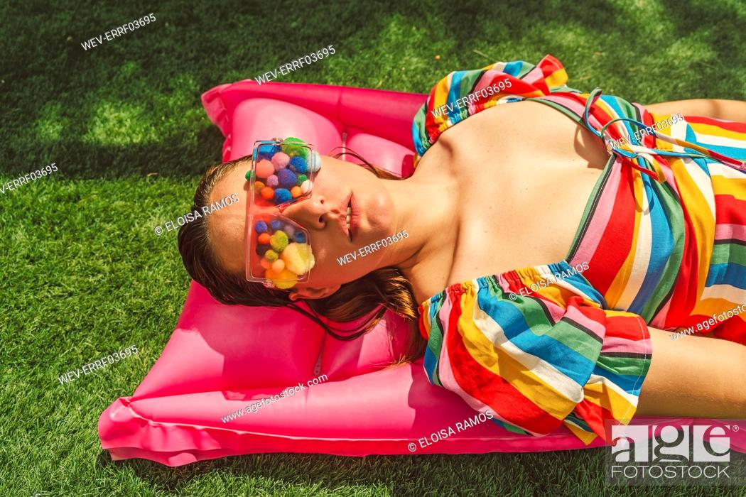 Stock Photo: Portrait of woman wearing glasses with colourful pom poms covering her eyes relaxing on pink airbed.