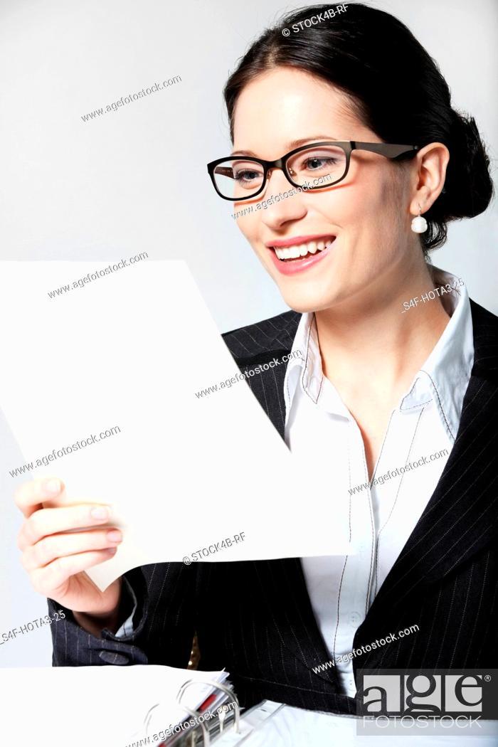 Stock Photo: Smiling businesswoman reading document.