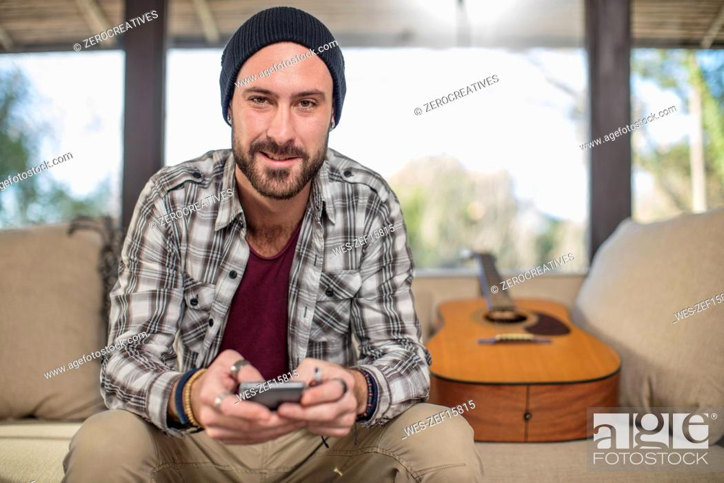 Imagen: Portrait of smiling young man at home sitting on couch with guitar using cell phone.
