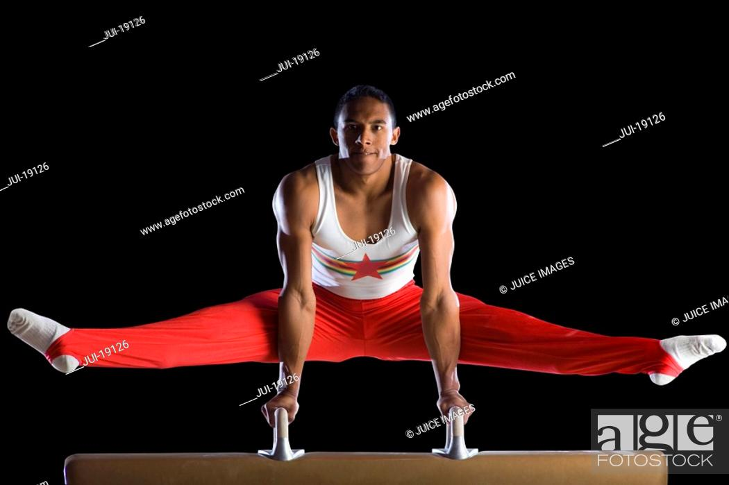 Stock Photo: Male gymnast performing on pommel horse, portrait, low angle view.