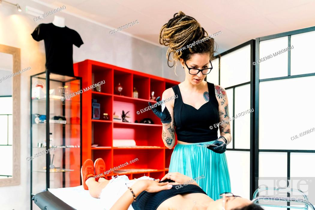 Stock Photo: Tattooist attending to customer in parlour.
