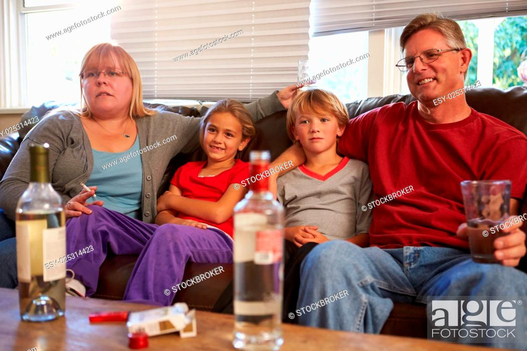 Stock Photo: Parents Sit On Sofa With Children Smoking And Drinking.