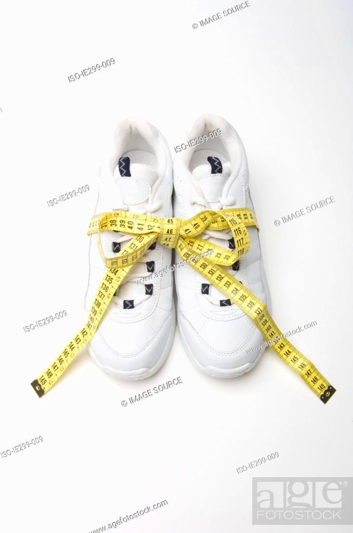 Stock Photo: Trainers and a tape measure.