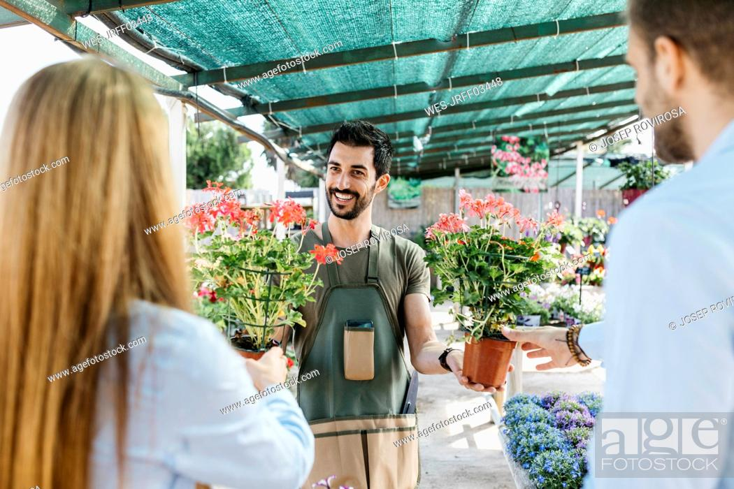 Stock Photo: Happy worker in a garden center showing plants to customers.