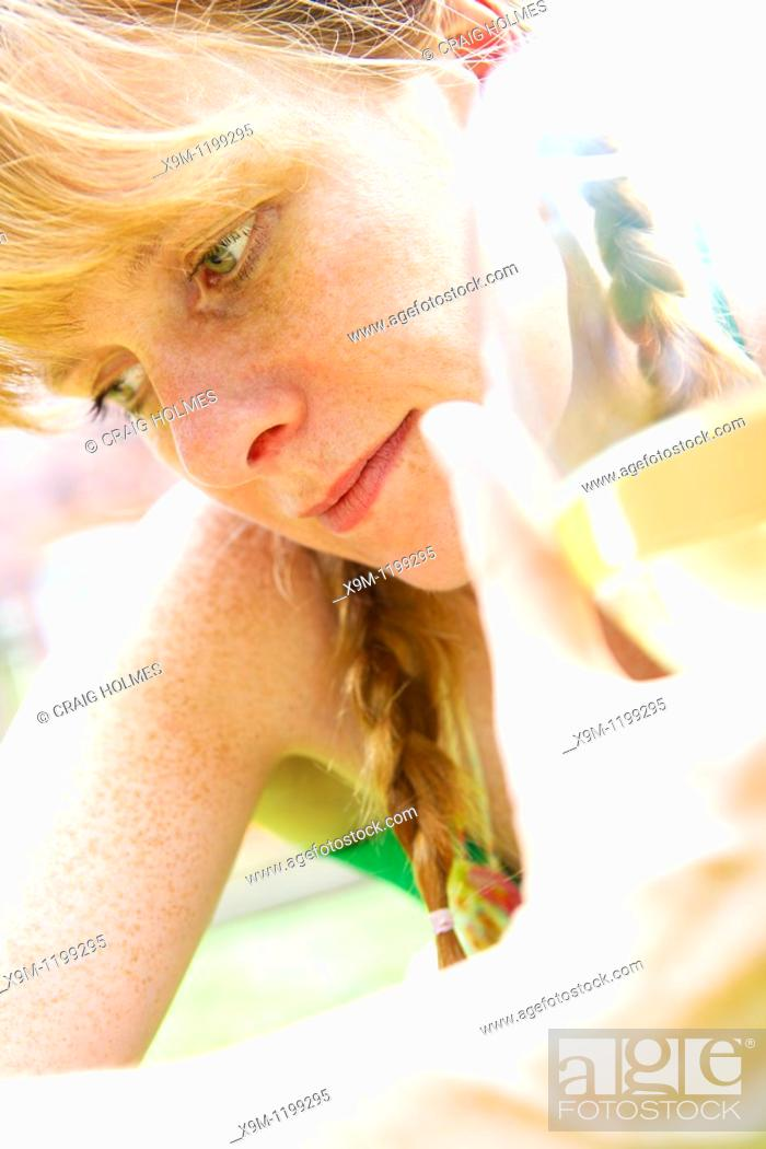 Stock Photo: Woman in her thirties drinking a glass of wine in her garden.