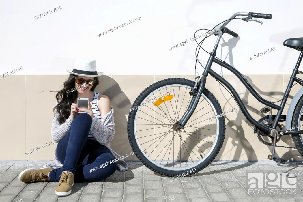 Stock Photo: Young cheerful woman in sunglasses and hat sitting nearby bike and using device. Lanzarote, Gran Canaria, Spain.
