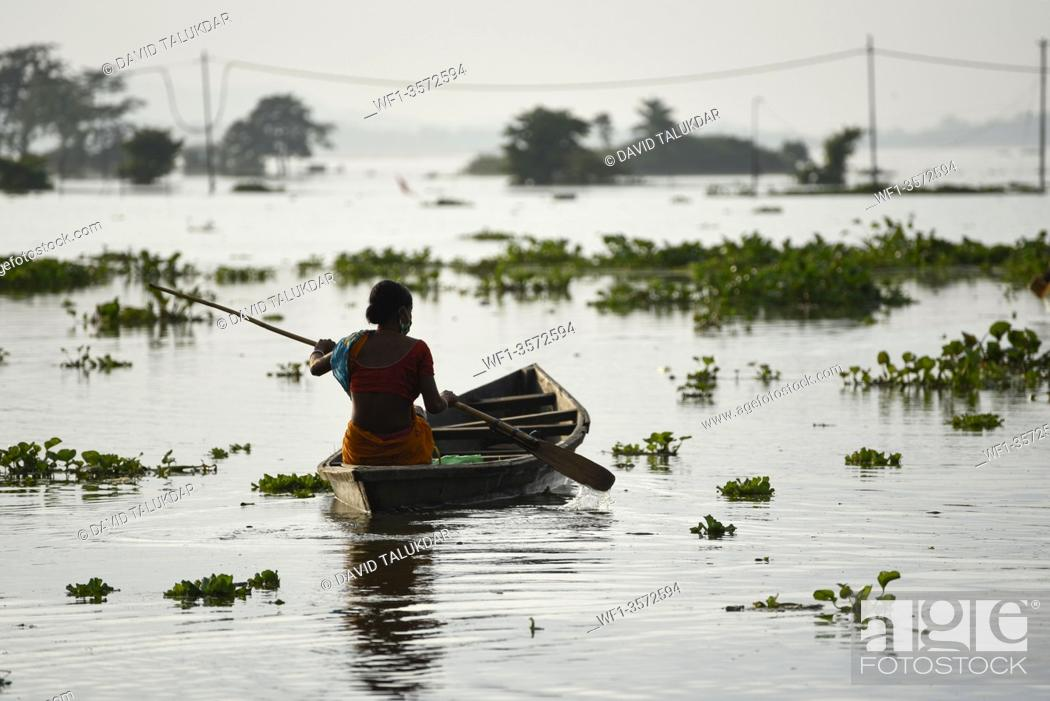 Stock Photo: A woman move to safer place from a flooded area in Kamrup district of Assam, Monday, July 13, 2020.