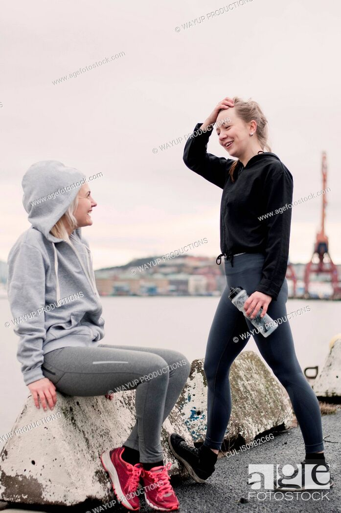 Stock Photo: Two female running friends chatting on dockside.
