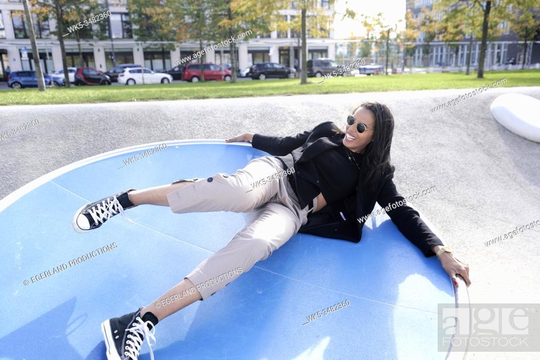 Stock Photo: Brazilian woman in playground, Munich, Germany.