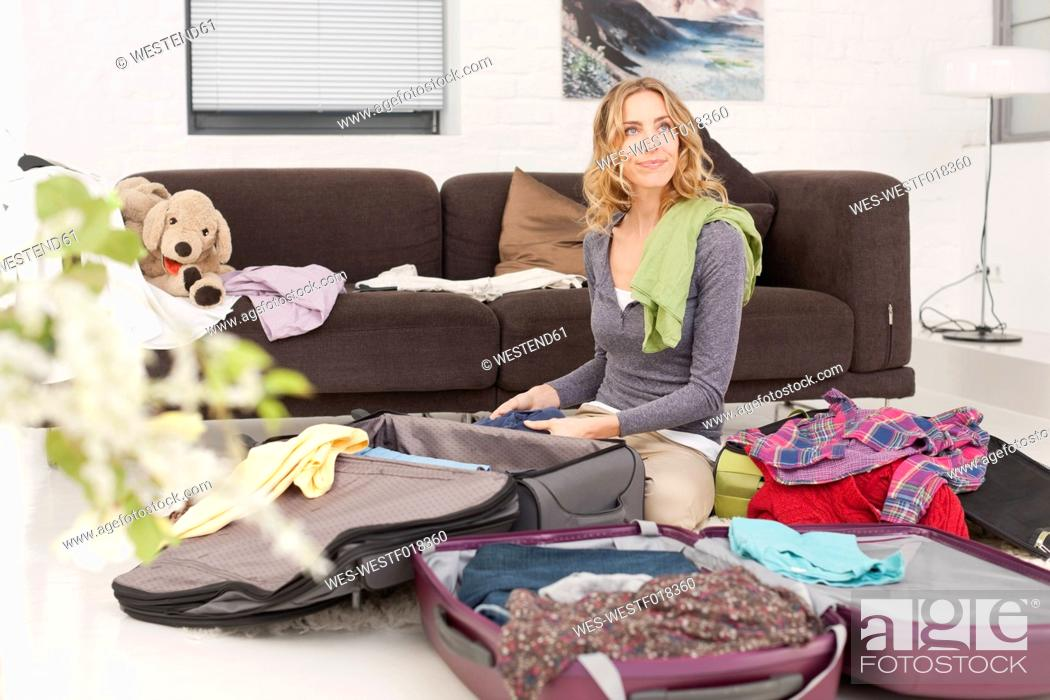 Stock Photo: Germany, Leipzig, Mid adult woman packing suitcase.
