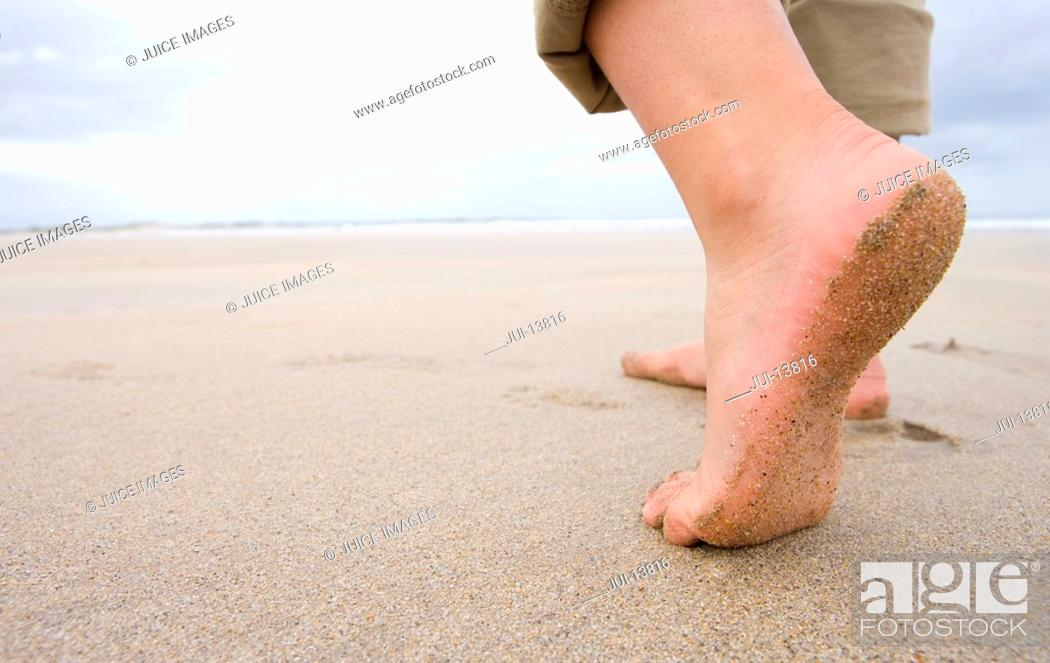 Stock Photo: Woman on beach, close-up of feet, low section.