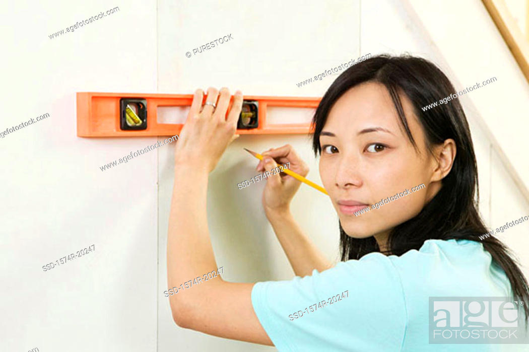 Stock Photo: Portrait of a young woman using spirit level to mark on a wall.