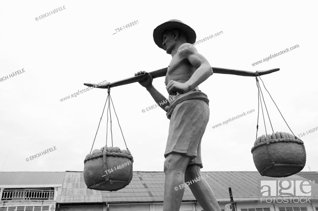 Stock Photo: Sculpture of a load carrier in Battambang.