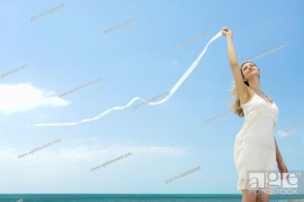 Stock Photo: Woman in sundress holding up ribbon in breeze, head back, eyes closed.
