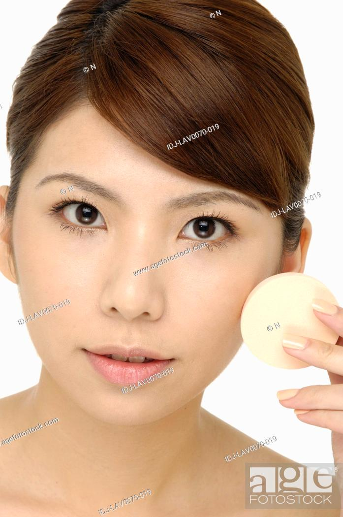 Stock Photo: Close-up face of beauty young woman applying face foundation.