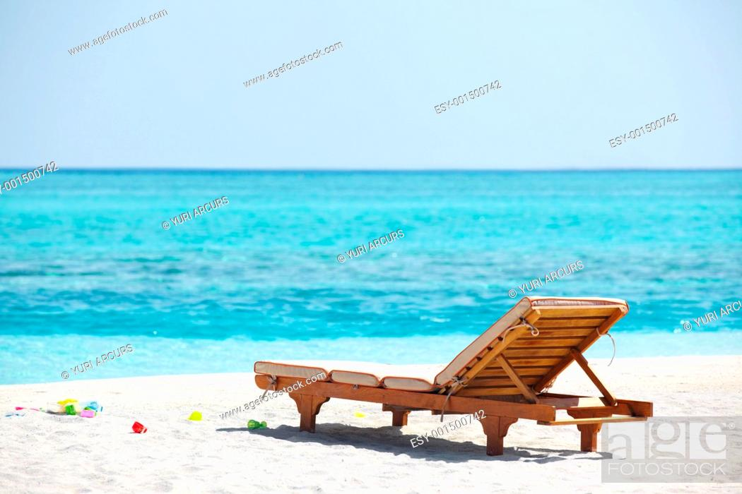 Stock Photo: Beautiful scene of one empty beach chair by the sea shore.