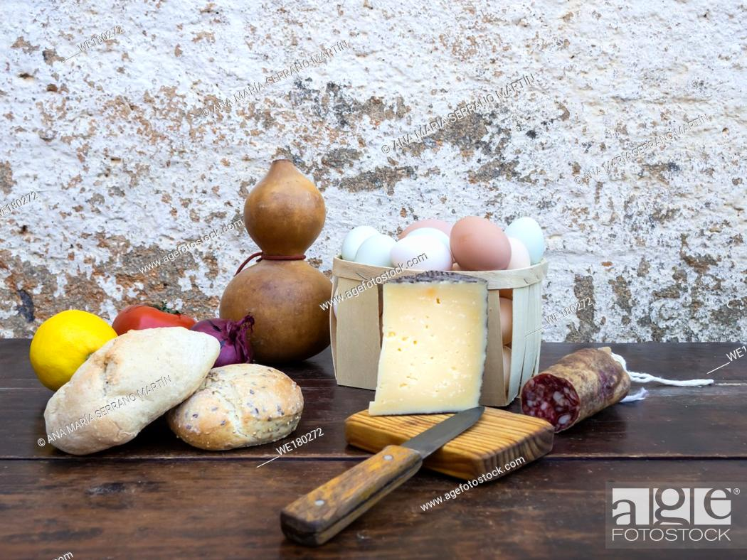 Stock Photo: Traditional spanish food on an old wooden table, Iberian pork sausages, bread, eggs, cheese and vegetables and an old knife.