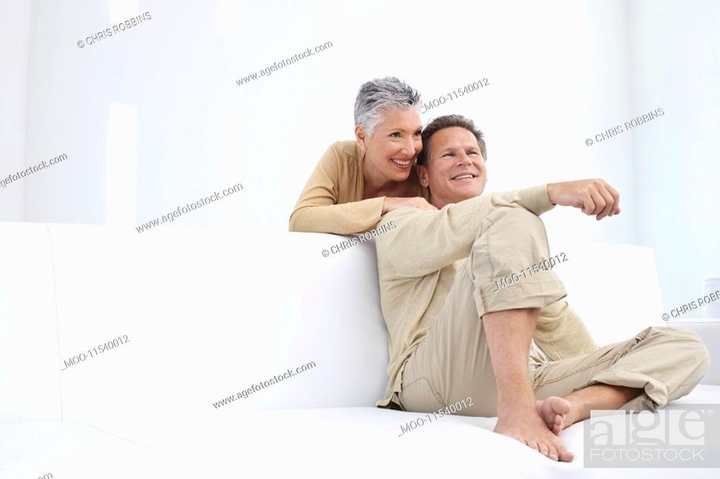 Stock Photo: Couple in living room smiling.