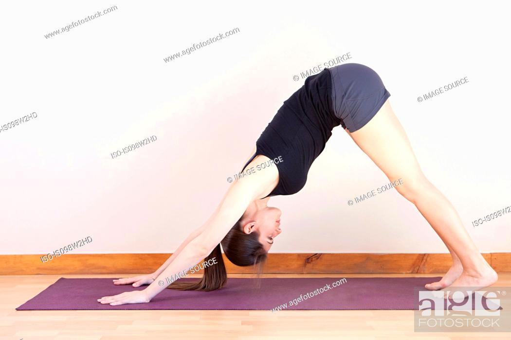 Stock Photo: Woman in downward facing dog position during yoga.