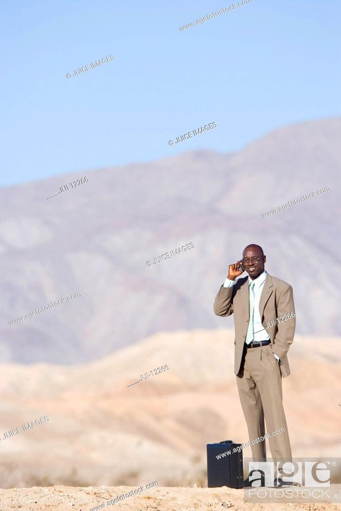 Stock Photo: Businessman by briefcase using mobile phone in desert, smiling.