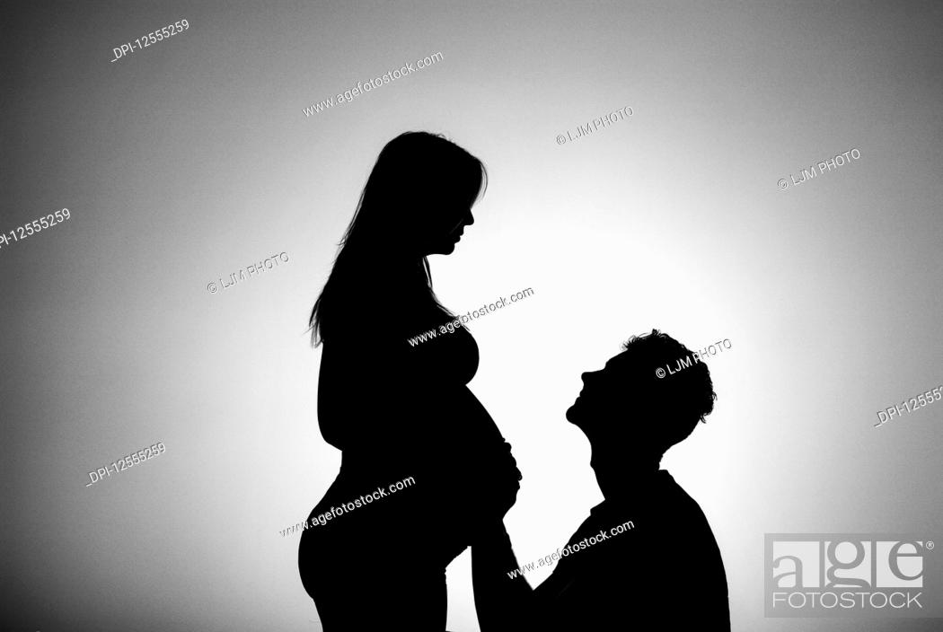 Stock Photo: A silhouette in a studio of a couple who are having a baby and the father is touching the mother's belly who is well along in her pregnancy; Edmonton, Alberta.