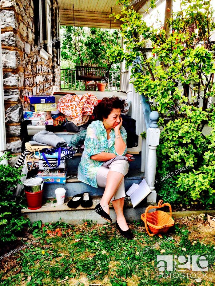 Imagen: A woman takes a rest at a yard sale.