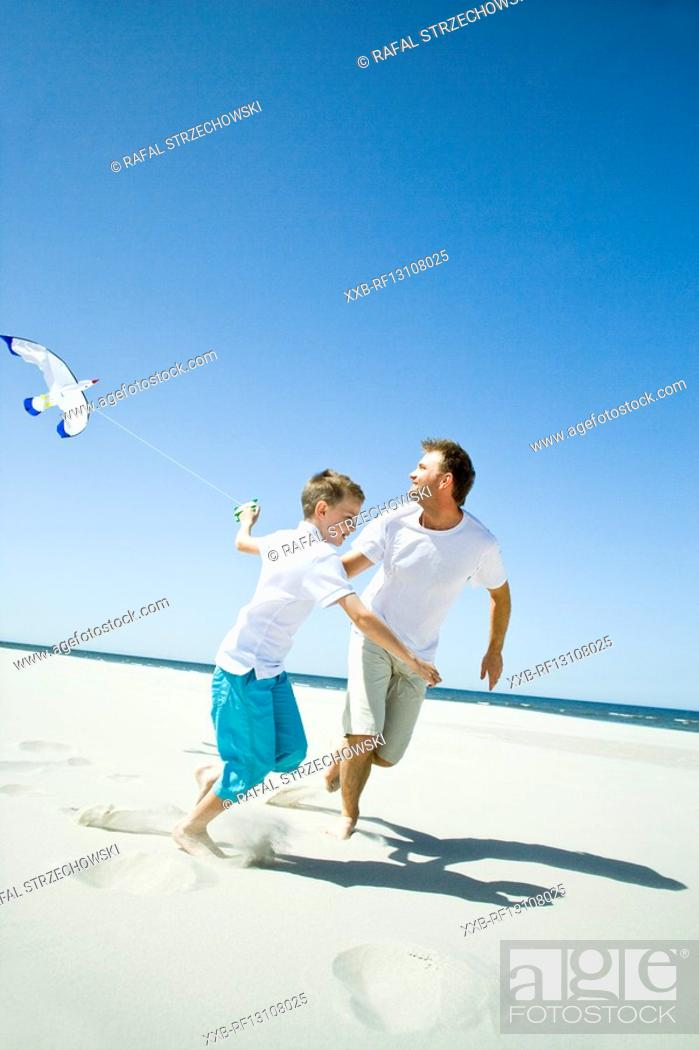 Stock Photo: father and son playing with kite on beach.