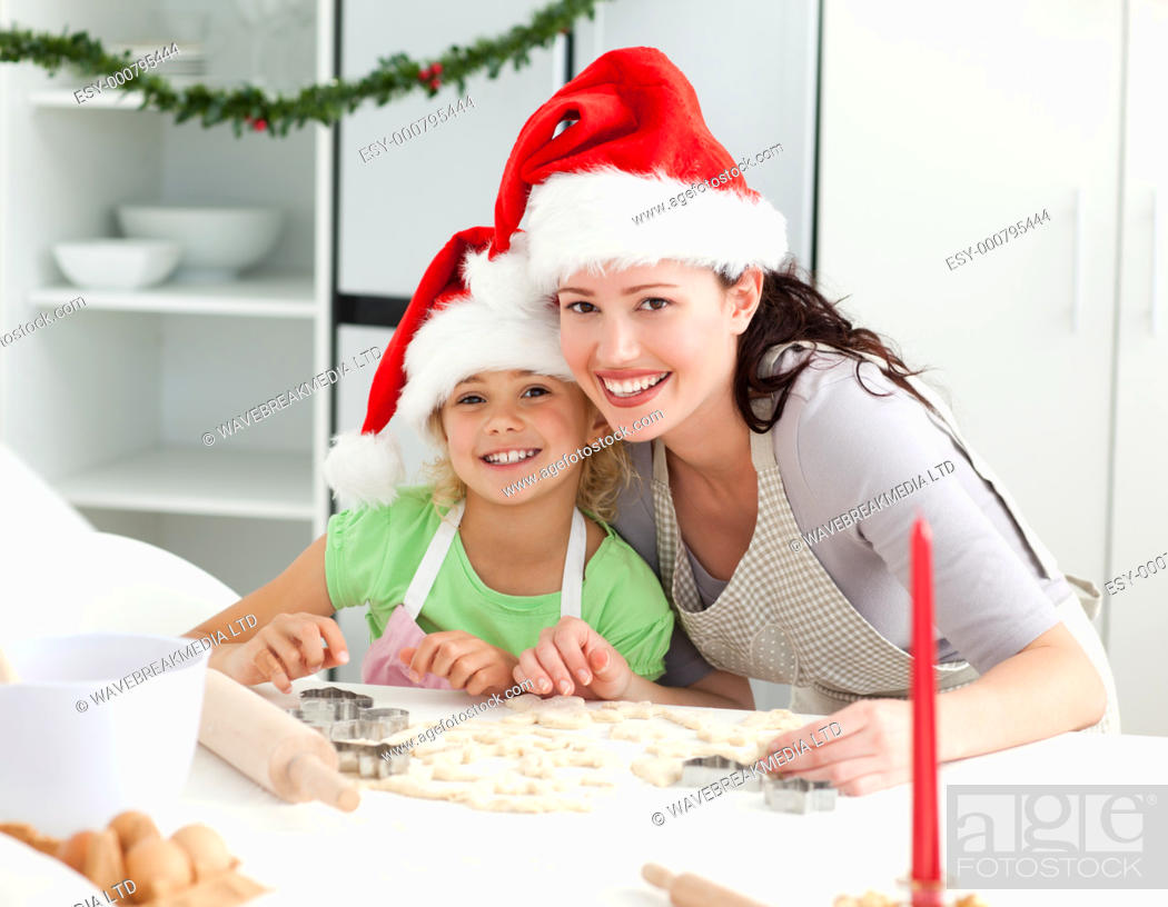 Stock Photo: Portrait of a cute girl with her mother baking Christmas cookies in the kitchen.