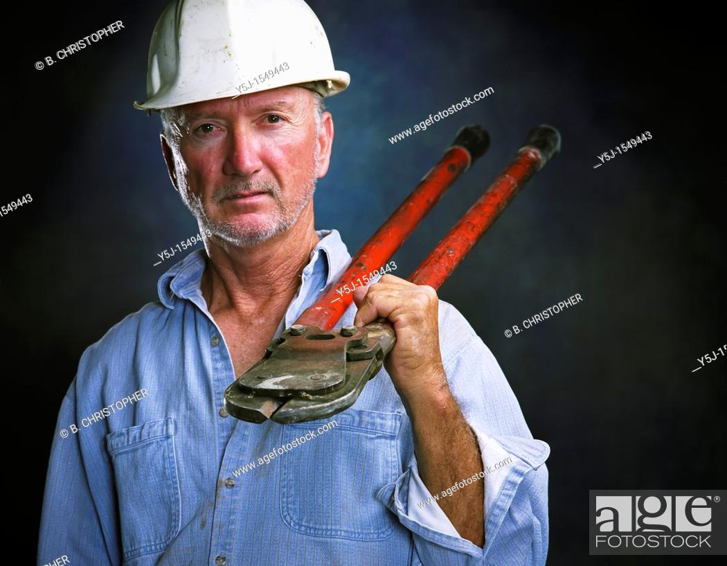 Stock Photo: Middle-aged laborer holding bold cutters.