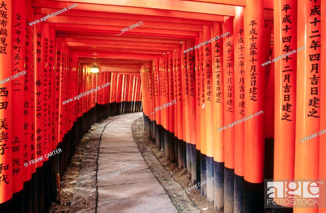 Stock Photo: A view of the many Tori gates that line the mountain pathway at Fushimi-Inari Shrine. Fushimi-Inari. Kyoto. Japan.