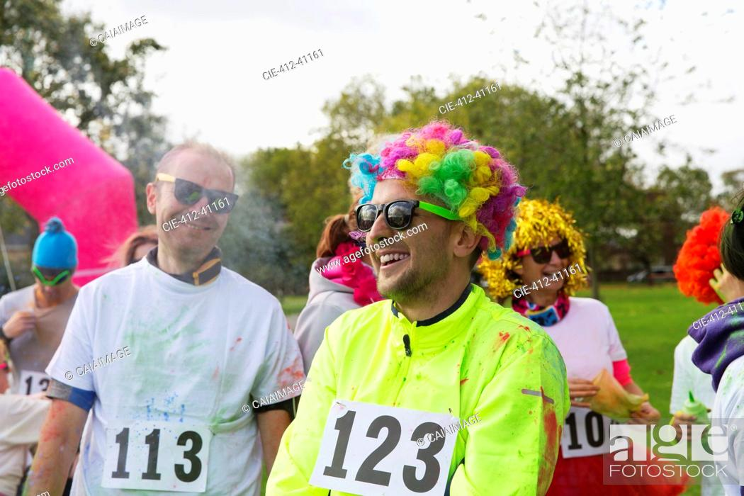 Stock Photo: Playful runner in wig at charity run in park.