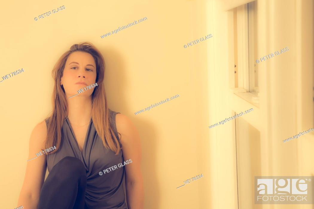 Stock Photo: Young woman, with long hair, near her window.