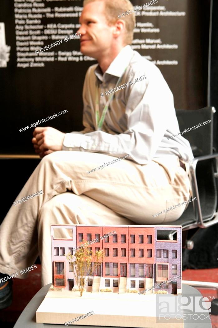 Stock Photo: View of a man sitting in front of an architectural model.