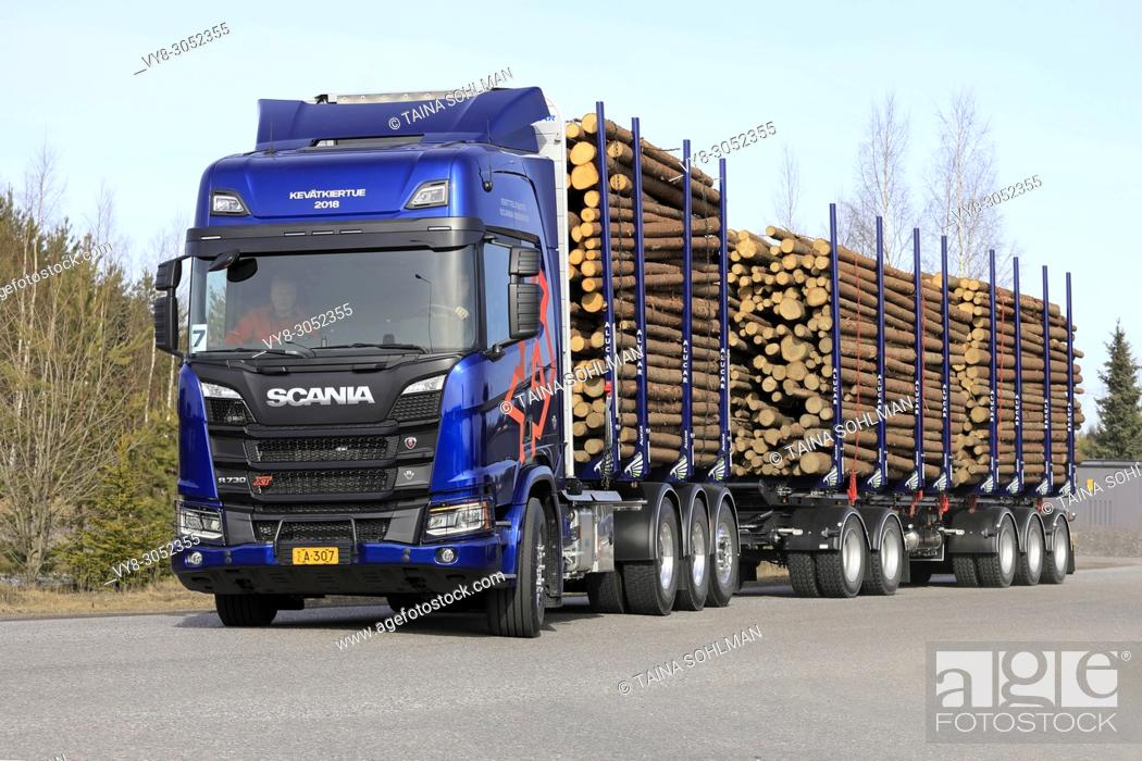 Stock Photo: Blue Scania R730 XT logging truck makes left turn on test drive during Scania Tour Turku 2018 in Lieto, Finland - April 12, 2018.