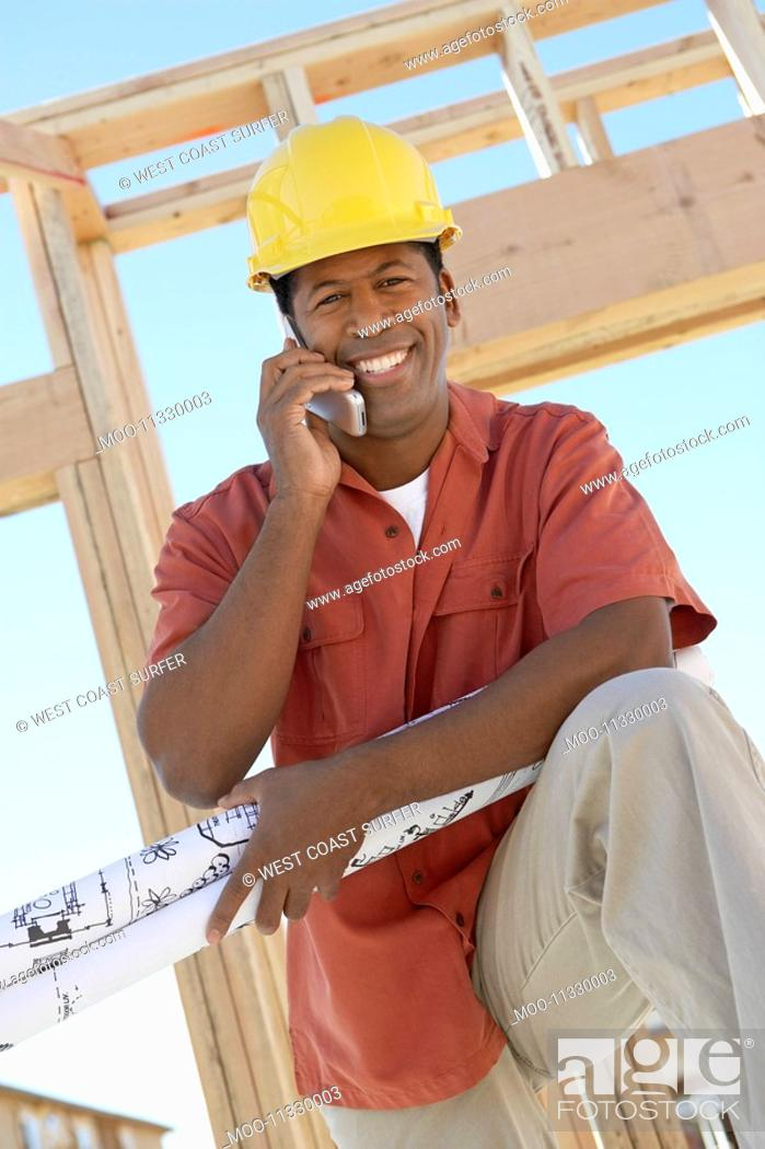 Stock Photo: Man on building site on cell phone.