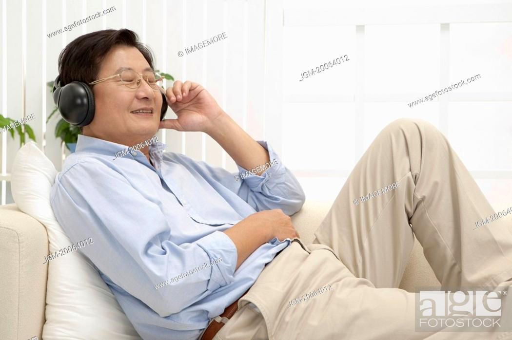Stock Photo: Husband, Man lying on sofa and listening music with smile.