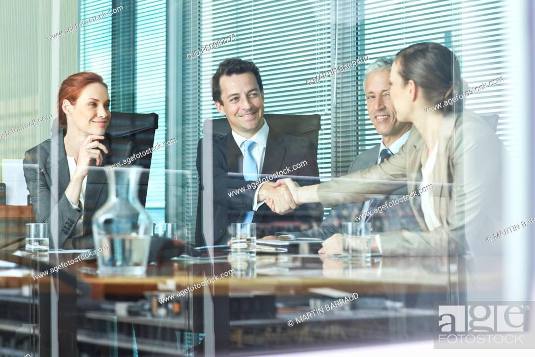 Stock Photo: Business people shaking hands at table in conference room.