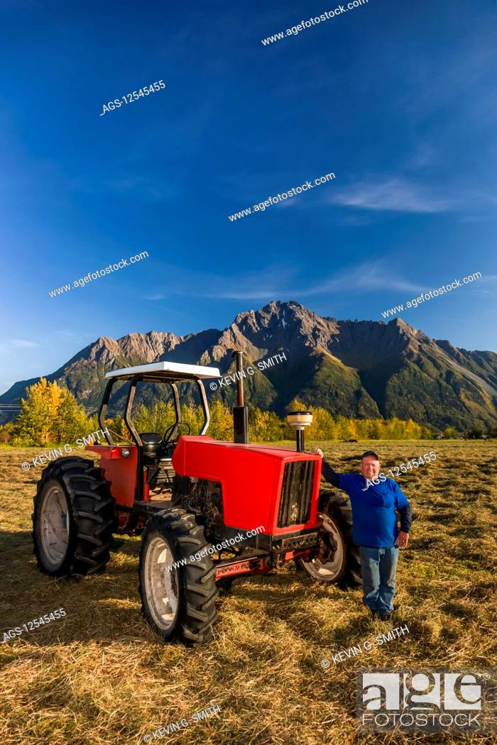 Stock Photo: A farmer wearing a blue shirt stands next to an old red tractor in an open field, Pioneer Peak in the background, South-central Alaska; Palmer, Alaska.