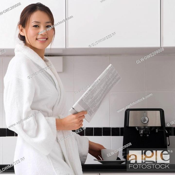 Stock Photo: Young woman holding a newspaper in the kitchen.