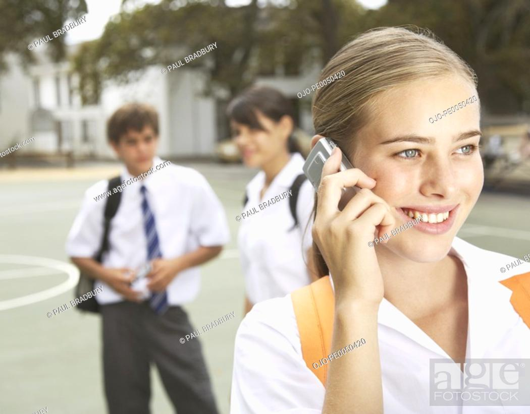 Stock Photo: Students outside their school one on a cellular phone.