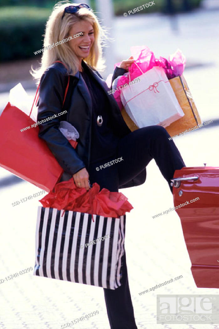 Stock Photo: Side profile of a young woman carrying shopping bags.