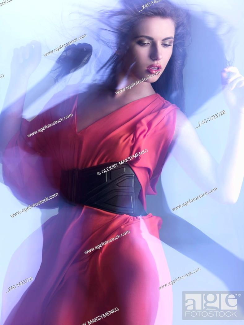 Stock Photo: Futuristic dynamic high fashion photo of a young woman in a red dress posing in shiny neon light settings  The photo was not digitally manipulated.