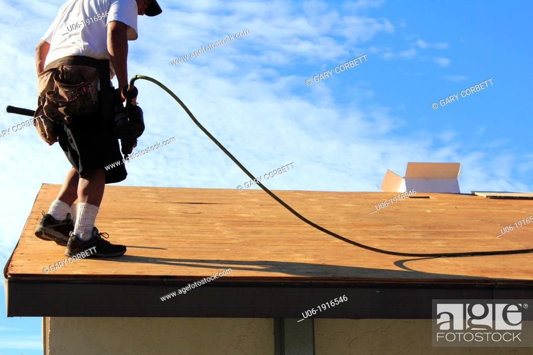 Stock Photo: a man or roofer using a nail gun and working to replace the plywood or wood or covering and shingles on a house roof.