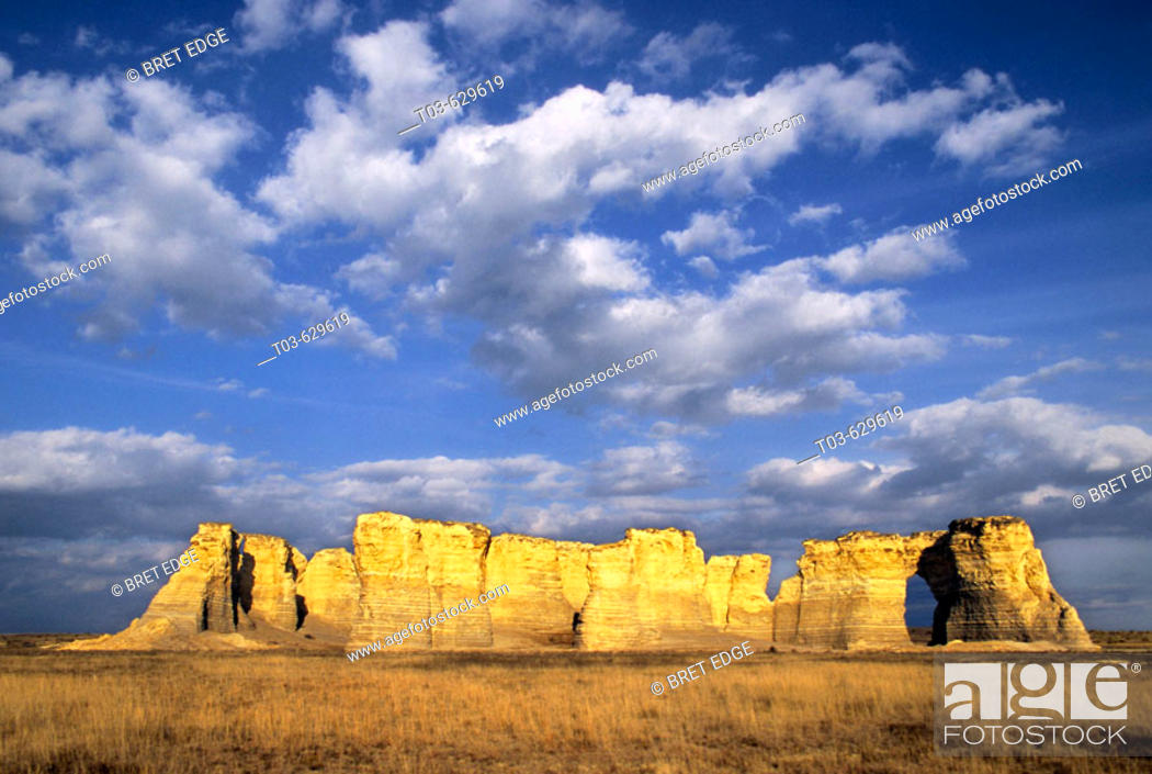 Stock Photo: Once buried beneath an ancient sea, Monument Rocks rises from the plains below a sky filled with cottonball clouds, Kansas, USA.