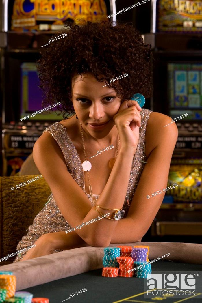 Stock Photo: Young woman gambling, holding gambling chip, smiling, portrait.