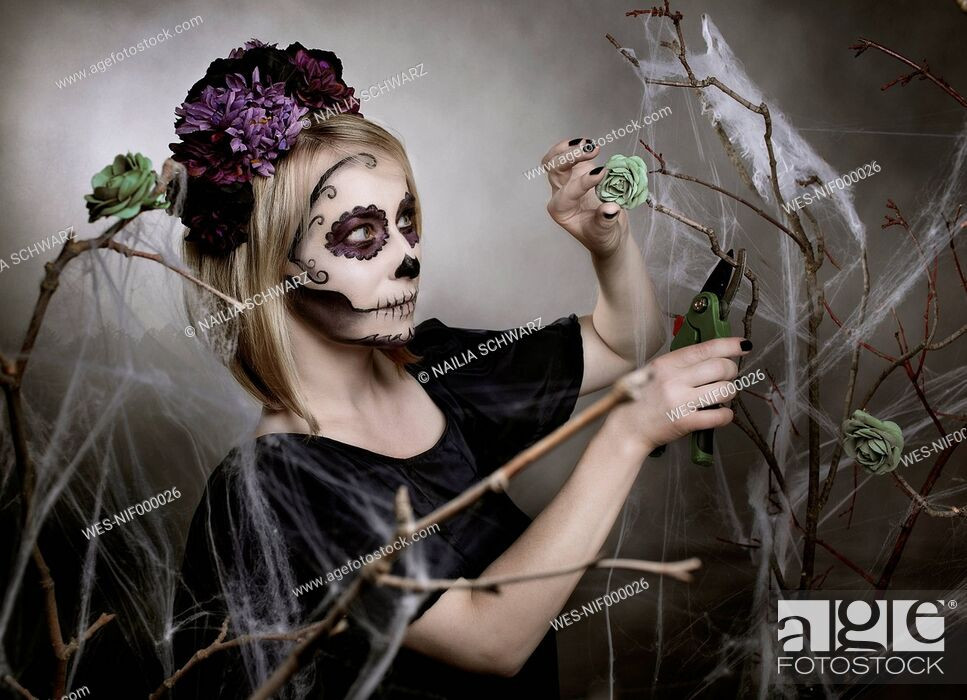 Stock Photo: Woman with sugar skull makeup cutting blossom with gardening clipper.