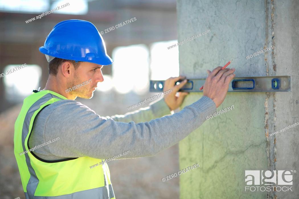 Stock Photo: Surveyor using spirit level on construction site pillar.