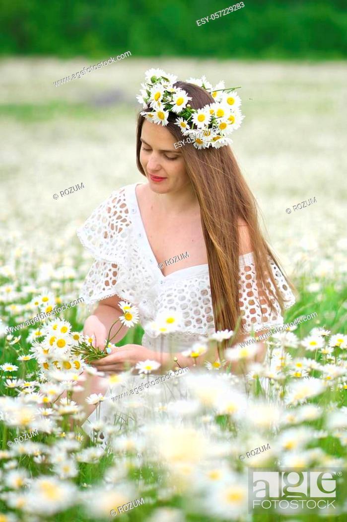 Stock Photo: Cute girl in camomile meadow. Beautiful outdoor portrait scene.