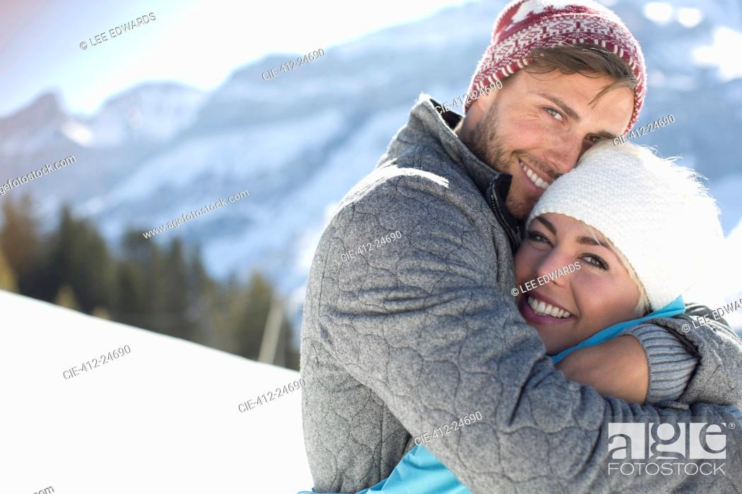 Stock Photo: Portrait of smiling couple hugging in snow.